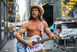 © Licensed to London News Pictures. 09/11/2016. New York CIty, USA. New York's naked cowboy, who is also a pro-Trump supporter celebrates the election results outside Trump Tower in New York City, on Wednesday, 9 November 2016 following the presidential election won by Donald Trump. Photo credit: Tolga Akmen/LNP