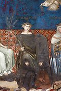 Allegorical figure of Fortitude, one of the Virtues of Good Government, wearing a black dress and a crown and holding a sceptre and a shield, below are 2 soldiers wearing armour and mounted on horseback. Detail from the fresco of the Allegory of Good Government (Allegoria del Buon Governo), from the series The Allegory and Effects of Good and Bad Government (L'Allegoria e Effetti del Buono e del Cattivo Governo), painted 1338-39 by Ambrogio Lorenzetti, c. 1290-1348, in the Sala dei Nove or Salon of Nine or Council Room, in the Palazzo Pubblico or Town Hall, Siena, Tuscany, Italy. Lorenzetti was commissioned by the Council of Nine to produce allegorical frescoes covering 3 of the 4 walls of their council chamber, and he produced 6 scenes on the 3 fresco panels. Picture by Manuel Cohen