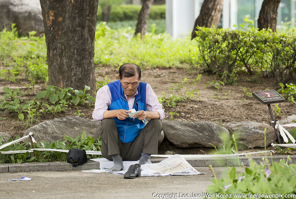 A man counts money at Tapgol Park in Seoul, South Korea on July 17, 2017. Photo by Lee Jae-Won (SOUTH KOREA) www.leejaewonpix.com