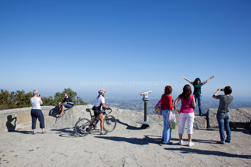 SAN MARINO, SAN MARNO - 3 OCTOBER 2011: Tourists watch the view of the Adriatic Sea and take pictures from the Prima Torre (First Tower) in San Marino, San Marino on October 3, 2011. The San Marino national football team is the last team in the FIFA  World Ranking (position 203). San Marino, whose population reaches 30,000 people, has never won a game since the team was founded in 1988. They have only ever won one game, beating Liechtenstein 1&ndash;0 in a friendly match on 28 April 2004. The Republic of San Marino, an enclave surronded by Italy situated on the eastern side of the Apennine Moutanins, is the oldest consitutional republic of the world<br /> <br /> <br /> ph. Gianni Cipriano