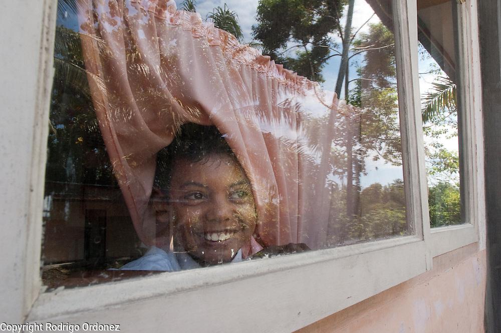 A boy peaks out of a window at School SDN 8 Nan Sabaris (Padang Pariaman district, West Sumatra, Indonesia).
