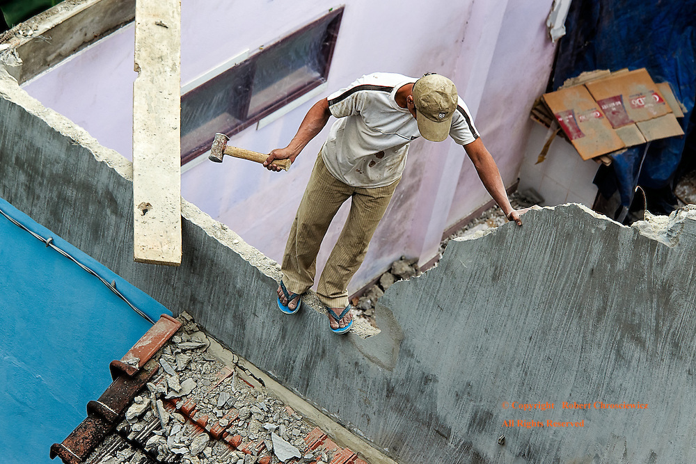 Safety Free: A demolition worker stands precariously on top of a wall, free of any safety precautions, wielding  a hammer against the very wall he is holding for balance and support, Hue Vietnam.