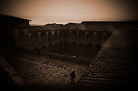 Sunset in the Lower courtyard within the Basilica of St. Francis of Assisi reveals a lone figure.  Piazza Inferiore San Francesco | Assisi Perugia, Italia.
