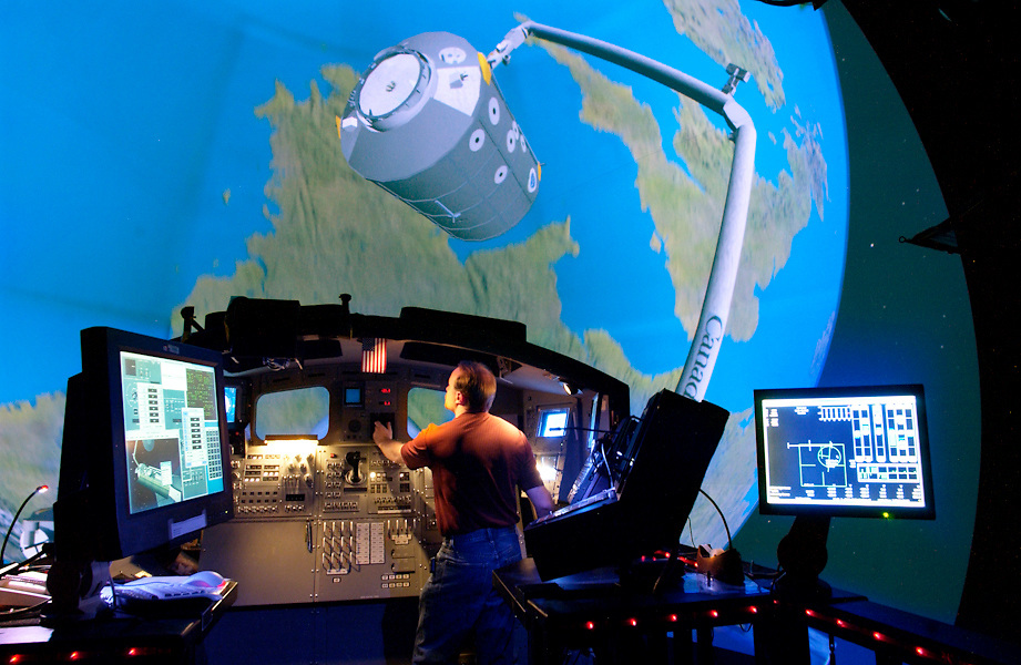 Russell Popejoy stands on the aft flight deck in the Shuttle Systems Engineering Shuttle Simulator as he operates the controls of the virtual robotic arm of the Space Shuttle.  His subject is a Multi Purpose Logistics Module that he wants to connect to and move to the International Space Station. The simulator is linked into a multiple digital image projector system that projects the moving image on to a dome shaped projection wall. The curved blue shape in front of the shuttle is a virtual image of earth.  (U.S. Air Force photo / Lance Cheung)