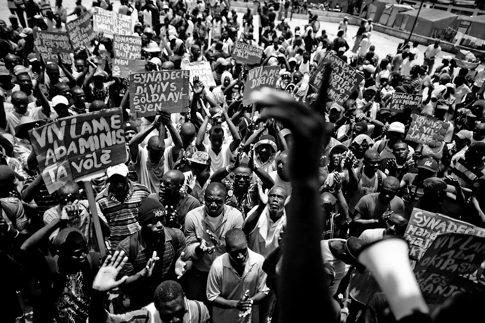 "Several hundred members of the unofficial Haitian Army block traffic and protest the UN's Military presence in Haiti chanting and carrying signs that say things like ""Minustah (UN peacekeeping mission) if you don't leave we will throw you out"", ""Stop the occupation"" and ""Minustah=Cholera=Army"". In a speach during the protest a leader called for Minustah to pay damages to those with cholera and then leave."