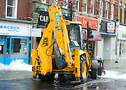 © Licensed to London News Pictures. 06/10/2014. Twickenham, UK . The JCB stemming the flood. Firefighters help to contain a mains water pipe which has burst in King Street Twickenham today 6th October 2014. It appears that workmen working in the area have used a JCB digger to stem the flow. Many local shops and businesses have been flooded.   Photo credit : Stephen Simpson/LNP