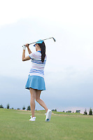 Rear view of woman swinging golf club at course
