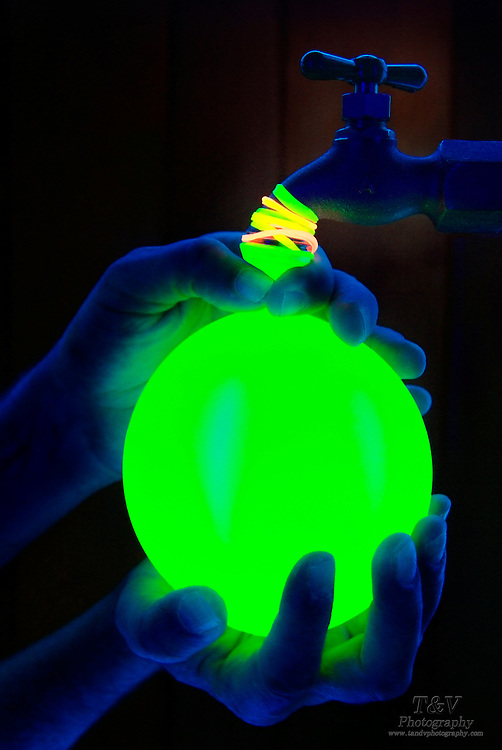 A glowing balloon is filled with water from a faucet.Black light