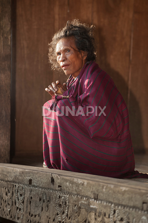 Old blind woman sits on her porch, Luba Village, near Bajawa, Flores, East Nusa Tenggara, Indonesia