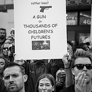 """Tens of thousands gathered in downtown Los Angeles to participate in the March For Our Lives protest march. Marches were held in over 800 cities worldwide to protest school shootings and advocate for gun control. The protest was organized after 17 kids were killed in a mass shooting at Stoneman Douglas High School in Parkland, Florida. Lauren Zeoli hugs her son, Kaine Zeoli, 12, who attends Lincoln Middle School, while speakers sing a tribute to the Parkland shooting. Amelia Teschner, 13, had her mom write on her face """"How Many More"""" in reference to how many more people must die from mass shootings before gun control measures are enacted."""
