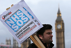 © Licensed to London News Pictures. 09/01/2016. London, UK.  A man holds NHS SOS placards during a rally against the proposed cancellation of bursaries for nurses hoping to train for work in the NHS.  Photo credit: Peter Macdiarmid/LNP