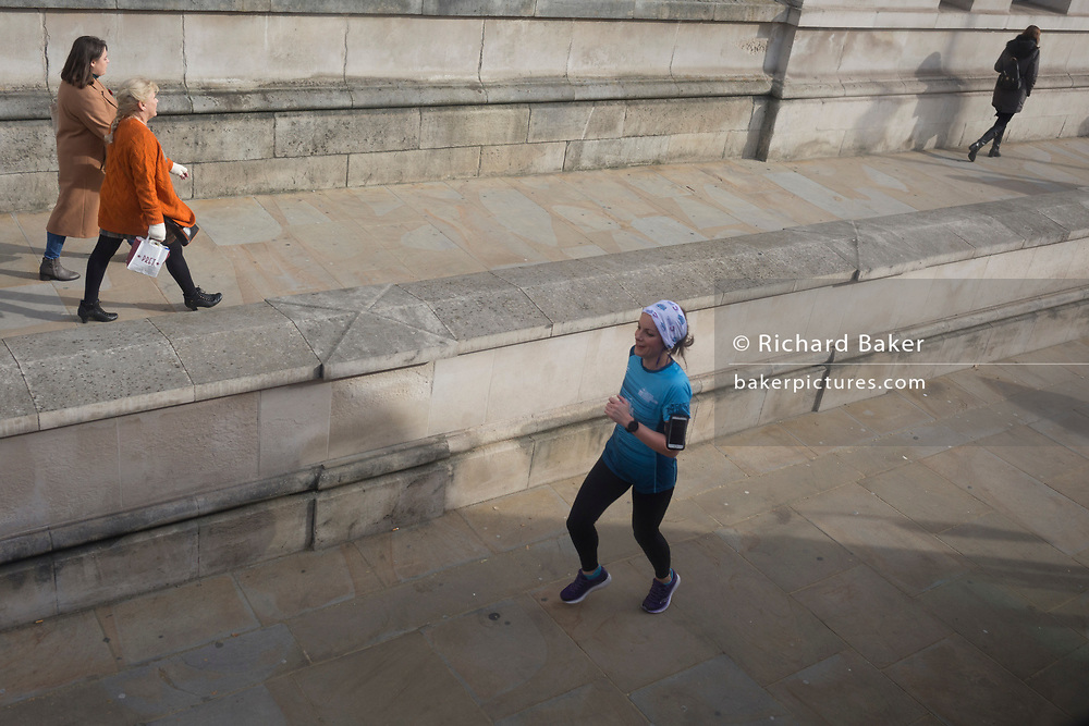 A lady runner jogs down Whitehall, on 28th October 2019, in Westminster, London, England.