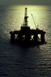 Offshore semi-submersible oil drilling rig silhouetted at sunset in Gulf of Mexico.