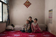 Jinshan Village<br /> Chen Xiuling (32) years old with her two children  He Yawen (9)<br /> and He Guanghui (6)<br /> Chen's husband is a migrant worker in the South of Gansu 4 hours by bus from the family home. He sets up electric lines in the countryside and comes back home every two months.<br /> They built a new house a year ago. She says the old house was warmer (the old house was made of adobe while the new one has concrete floors and walls) but she is still happy with the new one. The construction of the house is not finished so for now they are living in the smaller room.<br /> She met her husband in Lanzhou (the capital city of Gansu province) where they were both migrant workers. She subsequently moved to her husband's village where she is taking care of their children.