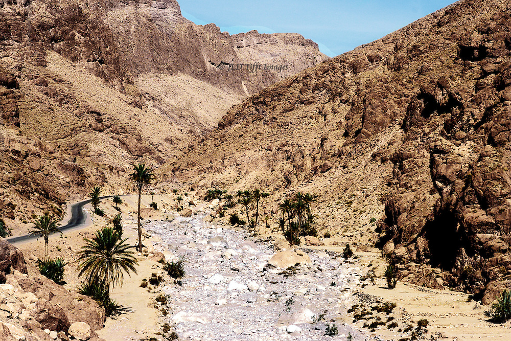Rocky stream bed alongside a narrow road through the High Atlas mountains.