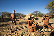A group of Bushmen preparing bows and arrows for hunting. Photographed in Namibia