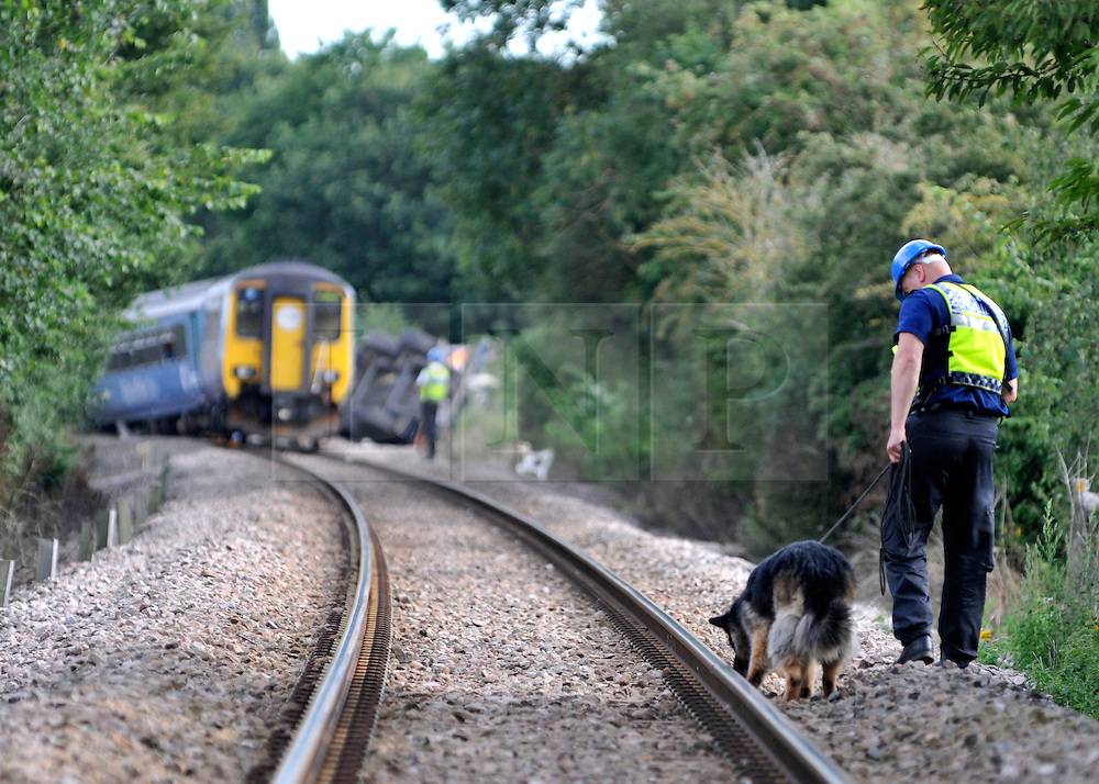 LITTLE CORNARD SUFFOLK.  Police dogs check the tracks in case dazed passengers have wondered off at the scene of the crash. Maintenece workers prepare to lift the two carriages and truck involved in yesterday's level crossing train crash in Little Cornard in Suffolk 18 August 2010. STEPHEN SIMPSON..