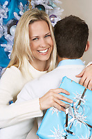 Woman with Christmas present hugging man