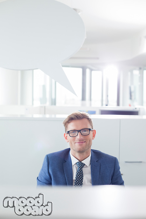 Portrait of confident businessman with speech bubble in office