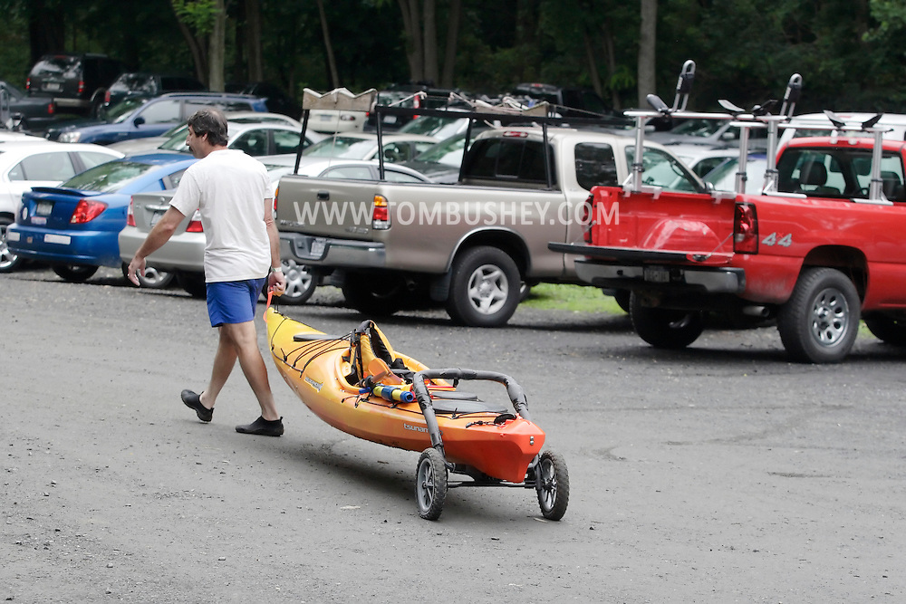New Windsor, New York - A man walks back to his car with his kayak after participating in the Hudson River at the Paddlefest event sponsored by the Mid-Hudson Chapter of the Adirondack Mountain Club at Kowawese Unique Area at Plum Point on  Sunday, June 13, 2010.