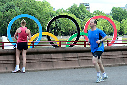 © Licensed to London News Pictures. 21/07/2012. LONDON, UK Giant Olympic Rings return to the Thames, beginning a series of appearances at key moments and different locations throughout the course of the Games. Rings are at Battersea for a number of days. Moored at Battersea Park, the coloured side is visible from the park.. Photo credit : Stephen Simpson/LNP