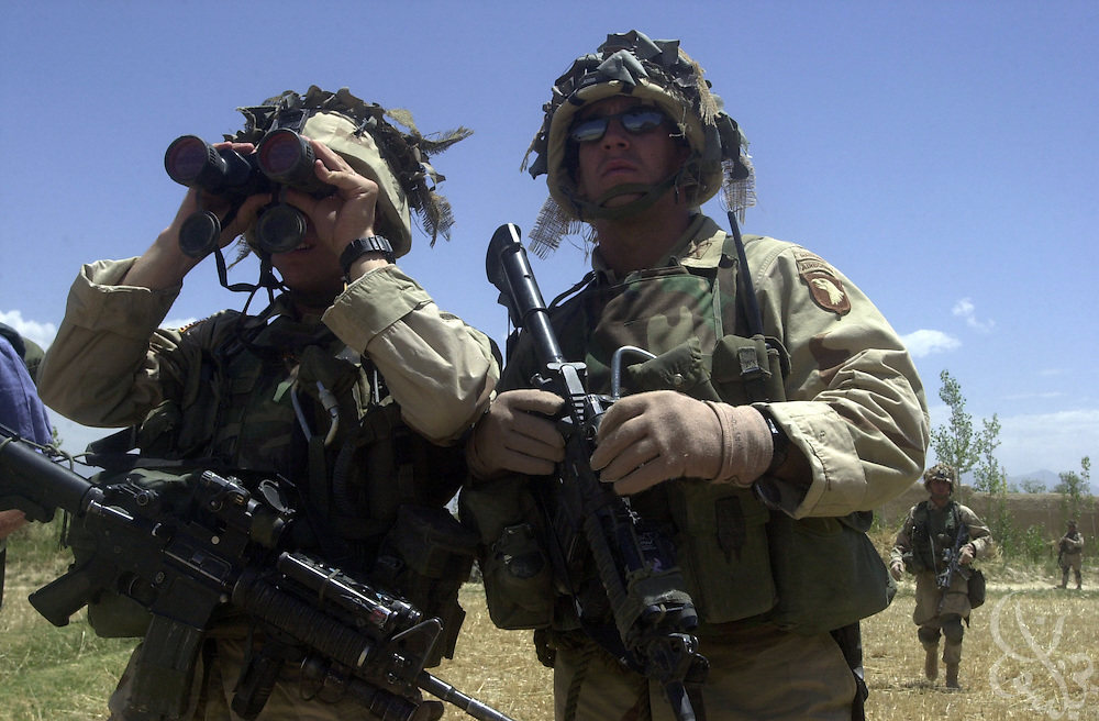 US Army soldiers from the 101st Airborne monitor the movement of two Afghan tanks near the eastern Afghan village of Hesarak on July 16, 2002 during what the Army refers to as a 'sensitive site exploitation' mission or 'SSE'. The army says that Hesarak was raided for the first time four days ago when undisclosed intelligence materials were gathered. Today's raid was intended both to search for more materials and to provide some hunanitarian aid to local residents.