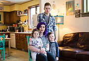 SHEBOYGAN, WI – February 3, 2019: Lauren Koch, center, sits for a portrait with her husband Trevor and two children, Luna and Jude, at their home in Sheboygan, Wisconsin, Sunday, February 3, 2019. Lauren takes care of her children at home while her husband works at a local restaurant.