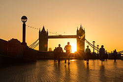 © Licensed to London News Pictures. 03/09/2017. LONDON, UK.  Morning commuters walk along the south bank during a golden sunrise this morning behind Tower Bridge on the River Thames, as the capital wakes up to a chilly and clear autumn morning. Photo credit: Vickie Flores/LNP