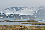Fannaråkbreen glacier flows across Fannaråken mountain (or Fannaråki, 2068-meters / 6785 feet elevation). The Norwegian national tourist road of Sognefjellsvegen (or Sognefjellsveien, Route 55, opened 1938) is the highest mountain pass in Northern Europe. It crosses between Jotunheimen National Park and Breheimen National Park, in Oppland and Sogn og Fjordane counties, Norway. The highest point is Fantesteinen at 1434 meters / 4705 feet.