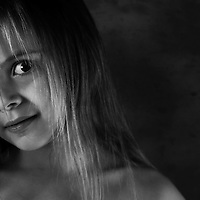 Young child looking at the camera with light shining on her face.