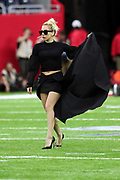 American singer, songwriter, actress and record producer Lady Gaga saves her black dress outfit as she poses for a photograph on the field while wearing sunglasses before the Atlanta Falcons Super Bowl LI football game against the New England Patriots on Sunday, Feb. 5, 2017 in Houston. The Patriots won the game 34-28 in overtime. (©Paul Anthony Spinelli)