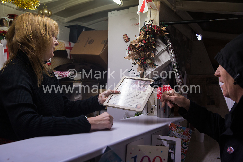 London, UK. 20 December, 2019. Cheryl Diamond looks at a photograph of Syd Tothill with the last customer of Syd's Coffee Stall, Dave Conway. The mahogany coffee stall, part of east London's history, has been run by three generations of the same family on the corner of Shoreditch High Street and Calvert Avenue since 1919 and will go on display in the new Museum of London in Smithfield in 2024.