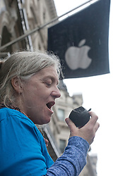 © licensed to London News Pictures. London, UK 25/04/2012. A Greenpeace activist posing like she is eating a plastic black apple which handed out to demonstrate against Apple's polluting coal usage to power their data centres, outside Regent Street Apple Store, this afternoon (25/04/12). Photo credit: Tolga Akmen/LNP