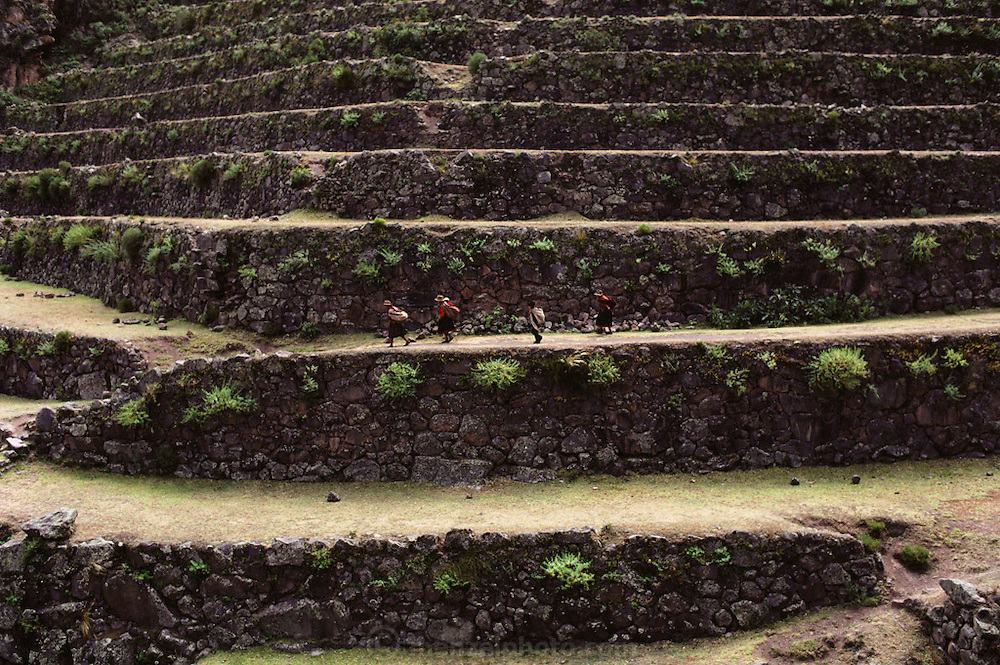 Villagers on their way to Sunday market pass thru the Inca ruins at Pisac, Peru.