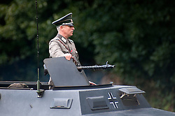 Reenactor dressed as a German Hauptman riding an Sd.Kfz 251 <br />