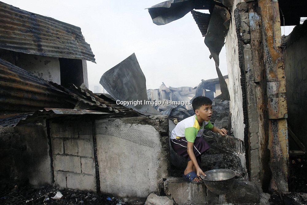 A boy collects useable materials from the slum area hit by a fire in San Juan City of Metro Manila, the Philippines, December 25, 2012. Photo by Imago / i-Images...UK ONLY
