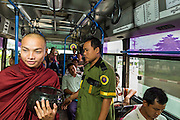 19 JUNE 2013 - YANGON, MYANMAR: A Buddhist monk walks past a fare collector on a Yangon bus. Yangon buses are generally overcrowded and in poor repair but as the economy improves newer, but still used, Japanese and Korean buses are being imported. Hundreds of bus routes criss-cross Yangon, providing the cheapest way of getting around the city. Most fares are less than the equivalent of .20¢ US.   PHOTO BY JACK KURTZ