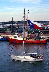 Sailboat with a large Texas flag sailing through the Kemah waterway