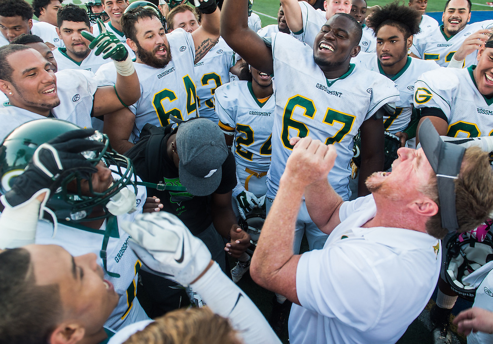 Grossmont head coach leads his players in post game celebration following their defeat of Santa Ana College, Thursday, November 6, 2014. (Photo: Bryan Woolston / @woolstonphoto)