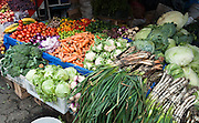 Produce market, carrots, cabbage, tomatoes, Otavalo, Ecuador, South America. The culturally vibrant town of Otavalo attracts many tourists to a valley of the Imbabura Province of Ecuador, surrounded by the peaks of Imbabura 4,610m, Cotacachi 4,995m, and Mojanda volcanoes. The indigenous Otavaleños are famous for weaving textiles, usually made of wool, which are sold at the famous Saturday market and smaller markets during the rest of the week. The Plaza del Ponchos and many shops tantalize buyers with a wide array of handicrafts. Nearby villages and towns are also famous for particular crafts: Cotacachi, the center of Ecuador's leather industry, is known for its polished calf skins; and San Antonio specializes in wood carving of statues, picture frames and furniture. Otavaliña women traditionally wear distinctive white embroidered blouses, with flared lace sleeves, and black or dark over skirts, with cream or white under skirts. Long hair is tied back with a 3cm band of woven multi colored material, often matching the band which is wound several times around their waists. They usually have many strings of gold beads around their necks, and matching tightly wound long strings of coral beads around each wrist. Men wear white trousers, and dark blue ponchos. Otavalo is also known for its Inca-influenced traditional music (sometimes known as Andean New Age) and musicians who travel around the world.