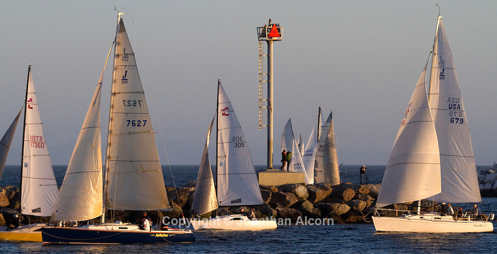 People stand on the breakwater and watch a group of sailboats enter Marina Del Rey on a perfect day for sailing, Wednesday, April 27, 2011
