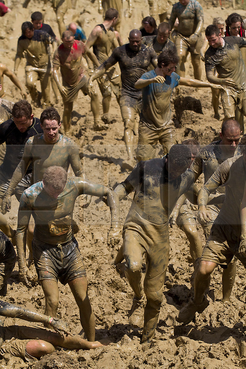 © Licensed to London News Pictures. 12/05/2012. Kettering, UK. Mud soaked Tough Mudder competitors work their way through the 'Mud Mile' challenge which consisted of hills and ponds of extremely wet mud. Thousands of people took part in Tough Mudder today (12/05) in the grounds of Boughton House, Northamptonshire. The 12 mile course which was designed by British special forces soldiers, consisted of 25 extreme obstacles including water, mud, electrocution, and high walls. The challenge is designed to test teamwork abilities as well as physical strength and stamina . Photo credit : James Gourley/LNP