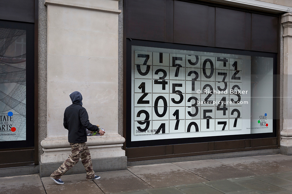A skateboarder walks past a window display that features numbers - part of a design theme called 'State of the Arts', at the Selfridges department store on Oxford Street, on 4th March 2019, in London England. Darren Almond's piece 'Chance Encounter 004', consists of a grid formed from rectangular panels, featuring fragmented numbers that appear to scroll across the surface. State of the Arts is a gallery of works by nine crtically-acclaimed artists in Selfridges windows to celebrate the power of public art. Each of the artists are involved in creating a site-specific artwork at one of the new Elizabeth line stations as part of the Crossrail Art Programme.