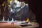 """THAILAND, Kao Luang: 09 November 2015 Visitors take a stroll through Tam Kao Luang """"Cave Kao Luang"""" this afternoon as natural sunlight enters from a hole above. The cave was consecrated to the memory of King Rama IV by his son King Rama V. Rick Findler / Story Picture Agency"""