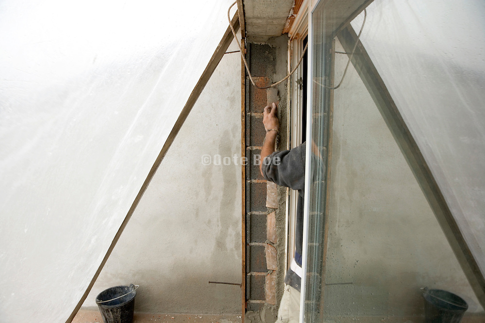 construction worker cementing a window pane with the outside protected by plastic