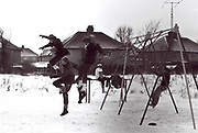 Teenage friends jump from swings on a snowy day at west London park. London, Greenford, UK, 1981.
