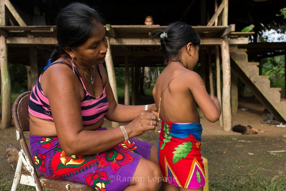 Mujer Embera realizando tatuaje tradicional a su hija.  Comunidad indígena La Chunga, Comarca Embera – Wounaan en la Provincia de Darién, Panamá.  La Chuga, ubicada en el  Rio Sambu, forma parte del corredor biológico de Bagres con sus inmensos bosques tropicales.