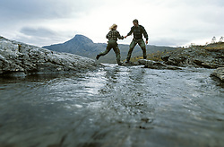 Woman passing brook, man giving a helping hand.<br /> Beiarn/ Norway.<br /> Released.