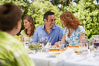 Family having meal at table in back yard
