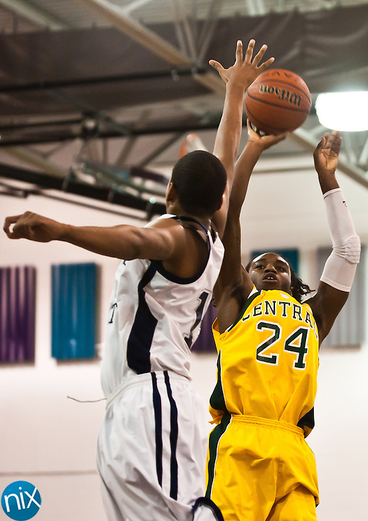 Central Cabarrus' Aaron Johnson tries to shoot over Queens Grant's Michael Gaskin during the championship game of the CMC-Northeast Holiday Classic Basketball Tournament at Cox Mill High School Thursday night. Queens Grant won the game 81-65. (Photo by James Nix)